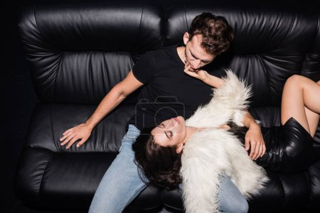 Passionate brunette woman in white jacket touching boyfriend chin, while lying on sofa in nightclub