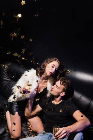 Passionate boyfriend holding woman jacket sitting on sofa, while confetti falling in nightclub