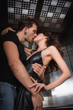 Low angle view of man hugging and kissing curly girlfriend in leather dress in elevator