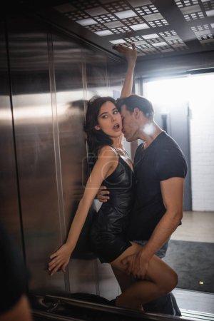 Photo pour Homme passionné embrassant et tenant jambe de femme séduisante avec les mains tendues regardant miroir dans l'ascenseur - image libre de droit