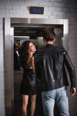 Photo for Back view of man in leather jacket and jeans standing near smiling brunette woman at elevator entrance - Royalty Free Image