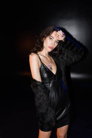 Photo for Curly brunette woman in jacket and leather dress posing with hand near head, while looking at camera on black - Royalty Free Image