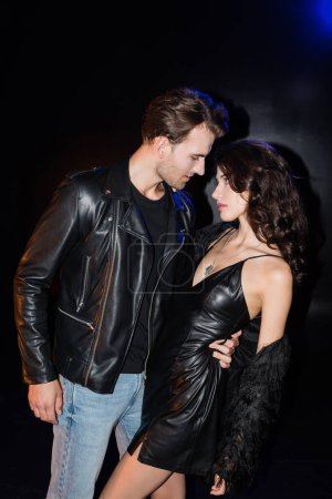Passionate boyfriend embracing and bending seductive girlfriend in leather dress on black