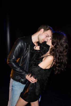 Passionate man in leather jacket bending and looking at lips of curly woman on black