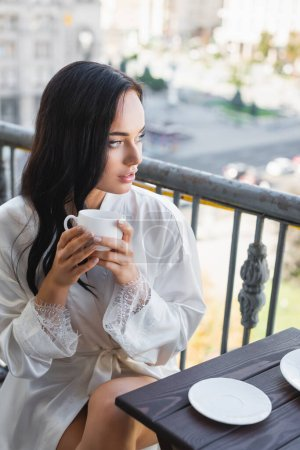 Photo for Beautiful brunette woman in white robe drinking coffee on balcony - Royalty Free Image