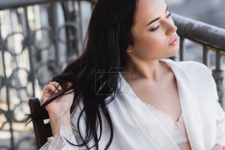 Photo pour Portrait de belle femme brune regardant loin et touchant les cheveux - image libre de droit