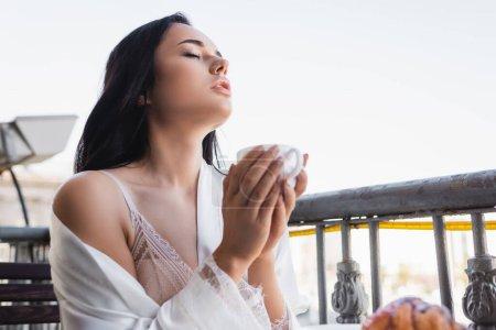 beautiful brunette woman enjoying drinking coffee with closed eyes