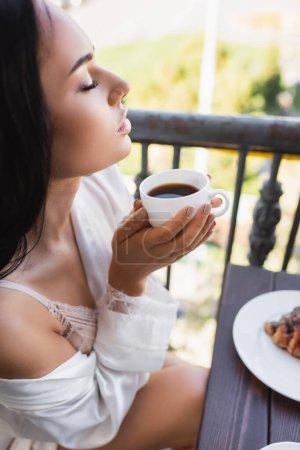 Photo pour Belle femme brune appréciant boire du café avec les yeux fermés - image libre de droit