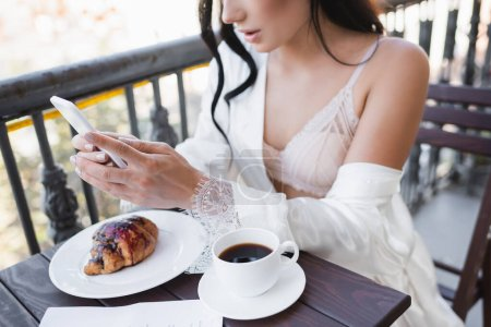 partial view of woman having breakfast on balcony and texting on smartphone