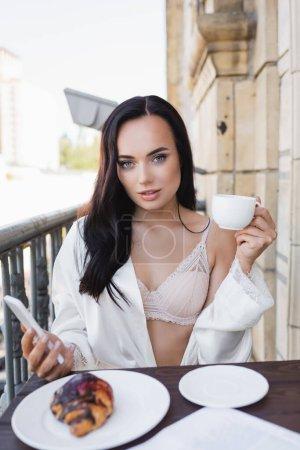 piękna brunetka kobieta w białym szlafroku gospodarstwa smartfon i śniadanie na balkonie
