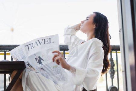Photo pour Femme brune en robe blanche assise sur le balcon et lisant le journal - image libre de droit