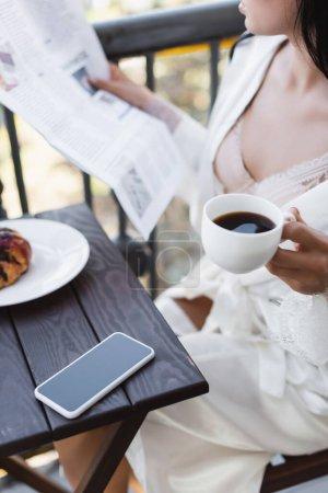 vista parcial de mujer morena en bata blanca bebiendo café y leyendo el periódico