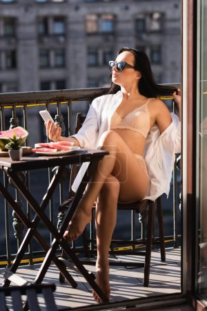 Photo for Sexy woman in beige underwear sitting on balcony and holding smartphone - Royalty Free Image