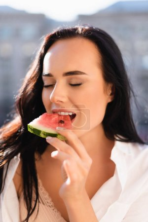 portrait of brunette woman eating watermelon with closed eyes