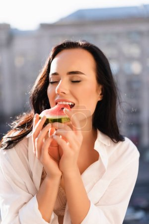 Photo for Brunette woman in beige underwear and white shirt eating watermelon with closed eyes - Royalty Free Image