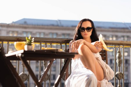 sexy brunette woman in sunglasses and covered in white sheet eating melon on balcony