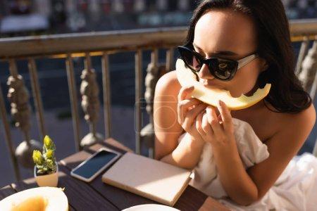 Photo pour Brunette femme en lunettes de soleil et recouvert de drap blanc manger melon sur le balcon - image libre de droit