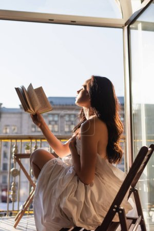 Photo for Attractive woman covered in white sheet reading book and sitting on balcony - Royalty Free Image