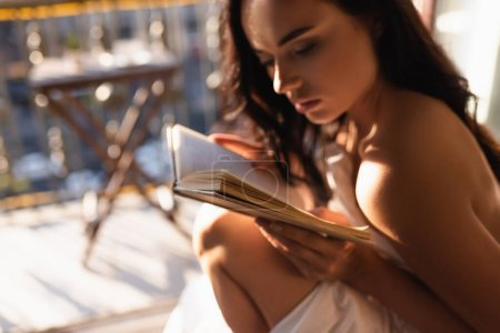 attractive woman covered in white sheet reading book and sitting on balcony