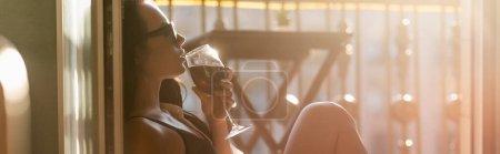 Photo pour Brunette femme en lunettes de soleil boire du vin sur le balcon, bannière horizontale - image libre de droit