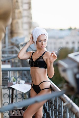 sexy young woman in black underwear with towel on head smoking cigarette on balcony