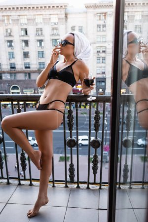 Photo for Sexy young woman in black underwear with towel on head smoking cigarette and drinking red wine on balcony - Royalty Free Image