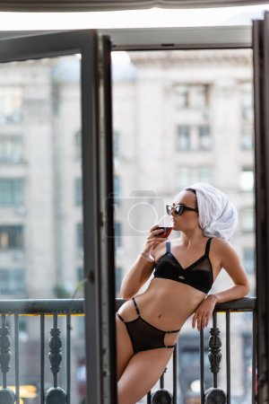 Photo for Sexy young woman in black underwear with towel on head drinking red wine on balcony - Royalty Free Image