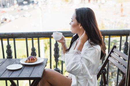 Photo pour Femme brune en robe blanche buvant du thé et assise sur le balcon - image libre de droit