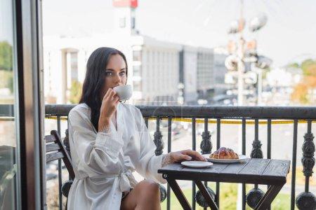 brunetka kobieta w biały szlafrok picia herbaty i siedzi na balkonie