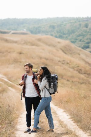 Photo for Smiling african american woman with backpack embracing boyfriend while hiking outdoors - Royalty Free Image