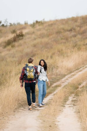 Photo for Smiling african american woman looking at boyfriend with backpack while walking on path during trip - Royalty Free Image