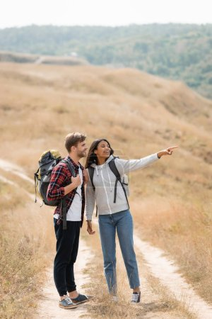African american woman pointing with finger near smiling boyfriend with backpack on path outdoors