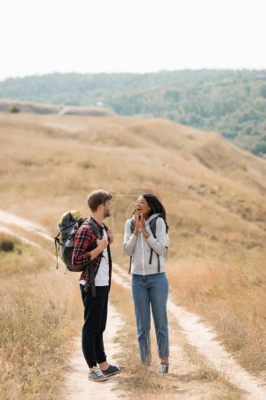 Photo for Cheerful african american woman standing near boyfriend with backpack on path during trip - Royalty Free Image