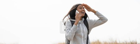 Photo for Cheerful african american hiker talking on smartphone outdoors, banner - Royalty Free Image