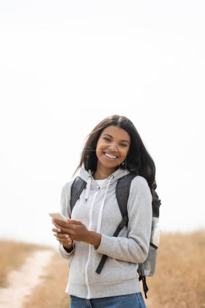Smiling african american tourist holding smartphone while looking at camera outdoors