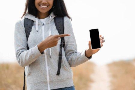 Photo pour Vue recadrée d'un touriste afro-américain souriant pointant du doigt un smartphone avec écran blanc à l'extérieur - image libre de droit