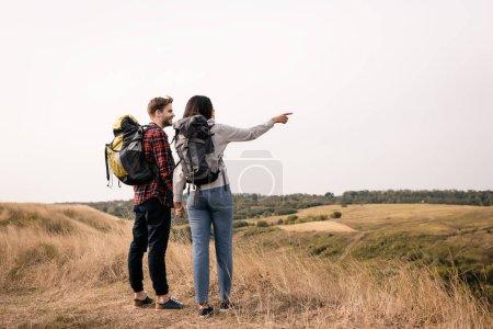 Photo pour Randonneur souriant tenant la main de la petite amie afro-américaine pointant du doigt avec des collines herbeuses sur fond flou - image libre de droit