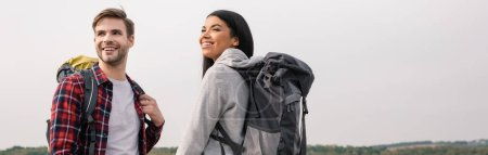Photo for Smiling multiethnic hikers with backpacks looking away outdoors, banner - Royalty Free Image