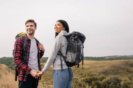 Photo pour Couple multiethnique souriant avec sacs à dos tenant la main avec des collines sur fond flou - image libre de droit