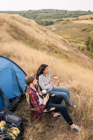 High angle view of smiling multiethnic tourists with cup and thermos sitting near backpacks and tent on lawn