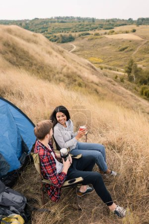 Photo for Smiling interracial couple holding cup and thermos near tent during camping in field - Royalty Free Image