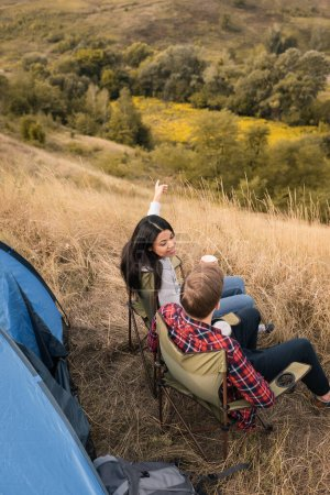 Photo for Overhead view of smiling african american woman with cup pointing with finger near boyfriend and tent on lawn - Royalty Free Image