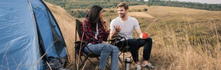 Photo for Smiling multiethnic couple with cup and thermos talking near tent during camping, banner - Royalty Free Image