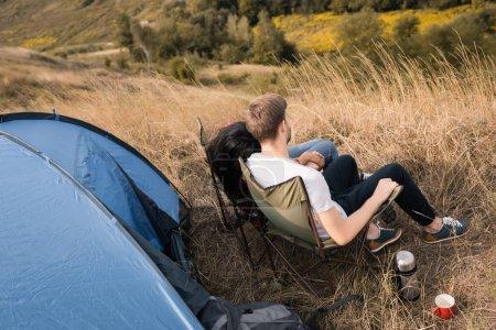 Photo pour Couple multiethnique tenant la main tout en étant assis près de tasse, thermos et tente sur prairie - image libre de droit