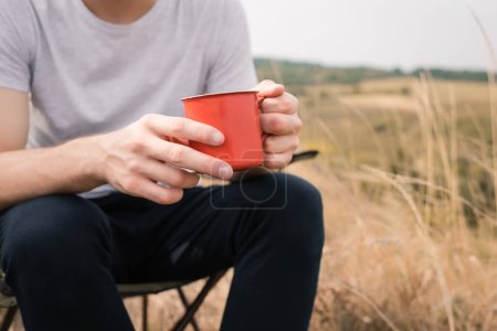 Photo for Cropped view of man holding cup while sitting on chair on lawn - Royalty Free Image