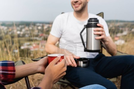 Cropped view of african american woman holding cup near smiling boyfriend with thermos on blurred background during camping