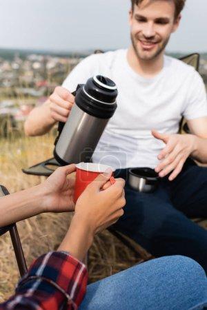 Photo pour Femme afro-américaine tenant une tasse près d'un homme souriant avec thermos au premier plan flou pendant le camping - image libre de droit