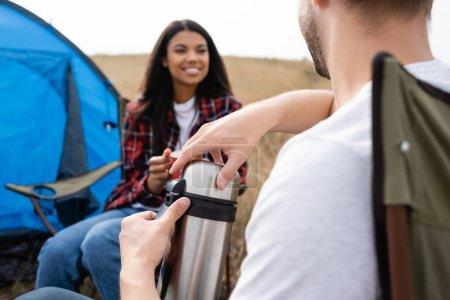 Photo pour Homme tenant thermos près de sourire femme afro-américaine sur fond flou pendant le camping sur prairie - image libre de droit