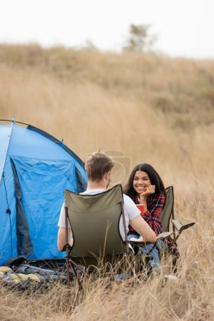 Smiling african american woman holding cup and looking at boyfriend near tent on grassy lawn