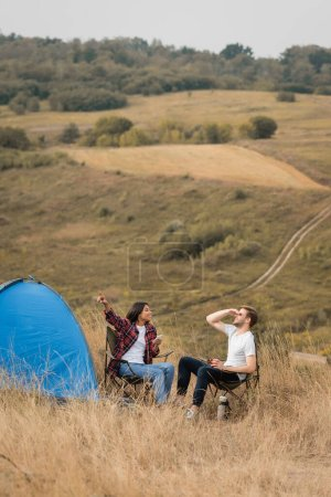African american woman pointing with finger while holding smartphone near boyfriend with cup and tent on meadow